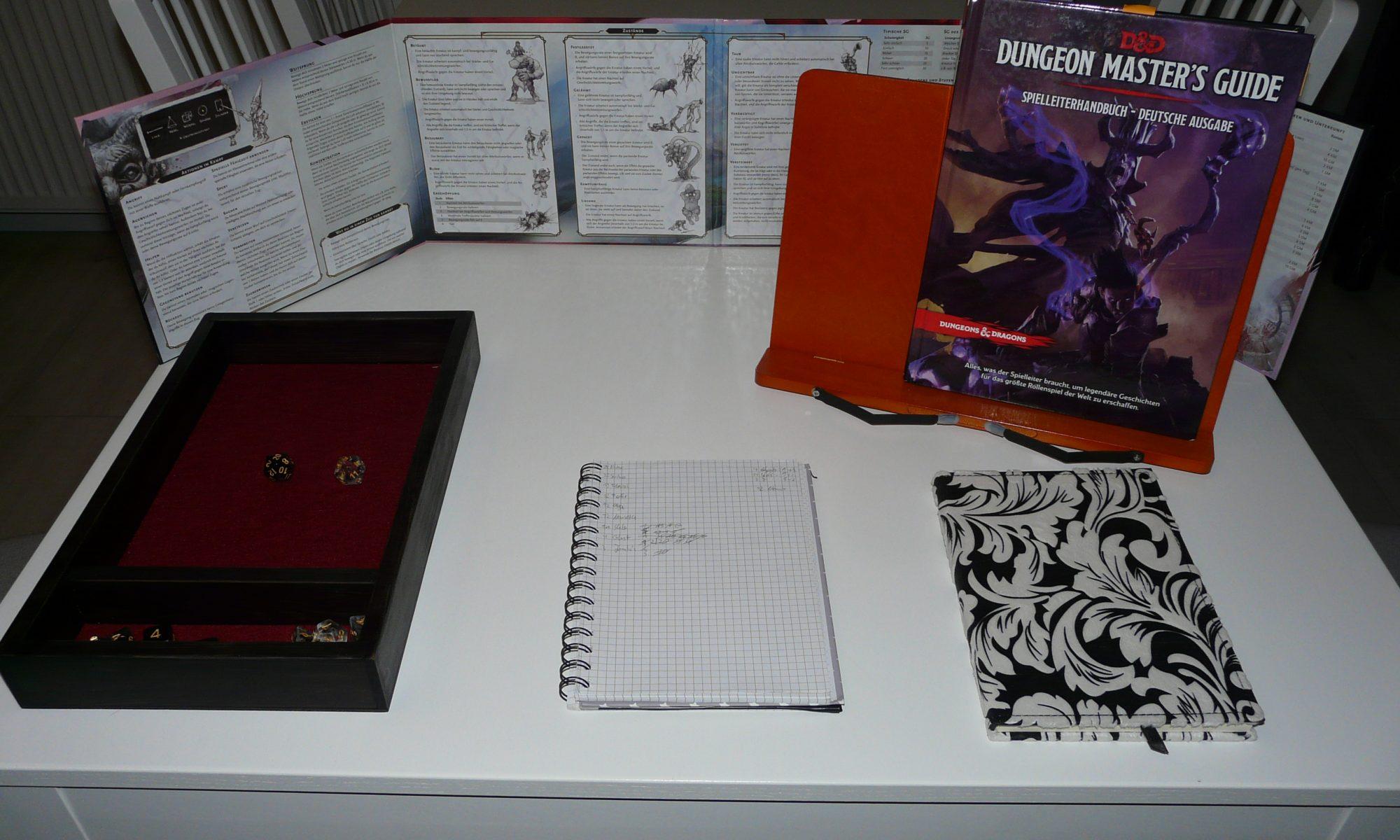 Das Bild zeigt ein Beispiel für das Setup eines Spielleiters oder einer Spielleiterin mit DM-Screen, Regelbuch, Dice Tray und Notizbüchern.