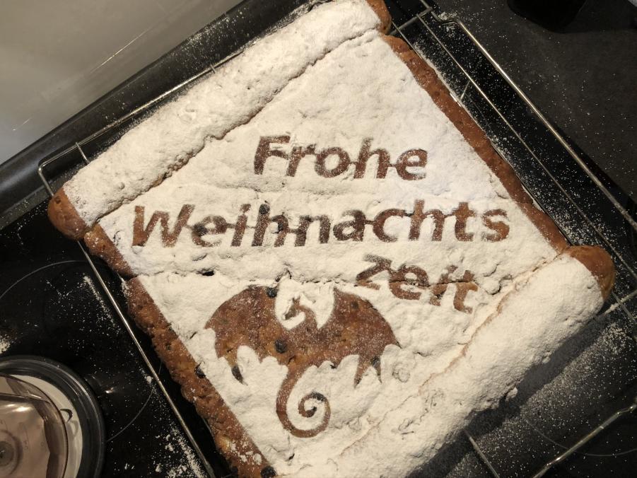"""Ein frisch gebackener Schrift-Stollen mit Puderzucker-Schrift """"Frohe Weihnachtszeit"""" und dem Bild eines Drachen."""
